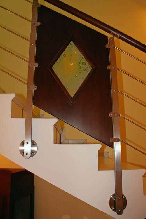 Ringhiera in acciaio inox per scala con pannelli in legno e vetro